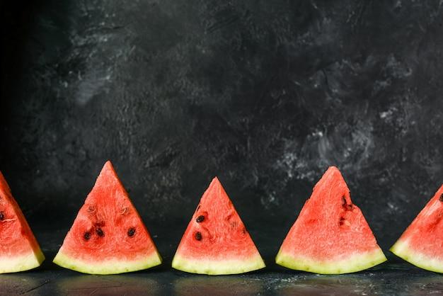 Nuttige bes zoete smakelijke ijslollys een plakje watermeloen in de zomer op een donkerblauwe rustieke achtergrond. kopieer ruimte voor ontwerper