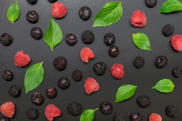 Nuttige bessen zijn zwarte en rode frambozen op zwart met bladeren