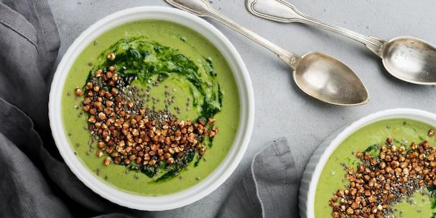 Nuttige smoothies van spinazie met boekweitvlokken in keramische kommen op grijze betonnen tafelondergrond. selectieve aandacht. bovenaanzicht. ruimte kopiëren.