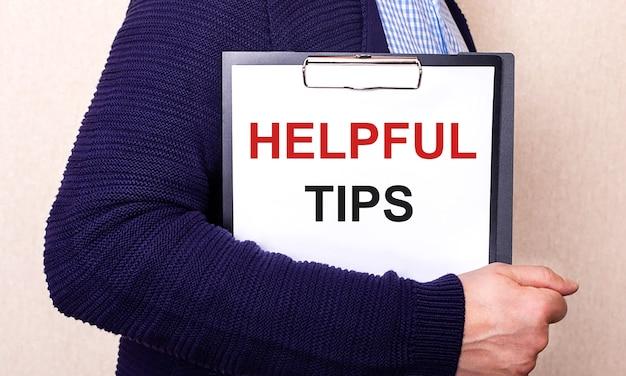Nuttige tips is geschreven op een wit laken dat wordt vastgehouden door een man die zijwaarts staat