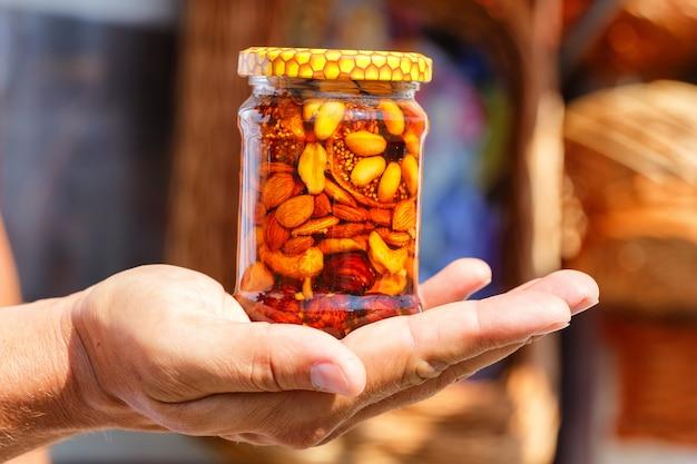 Nuttige zoetheid, noten in honing in een glazen pot, een man houdt in zijn hand