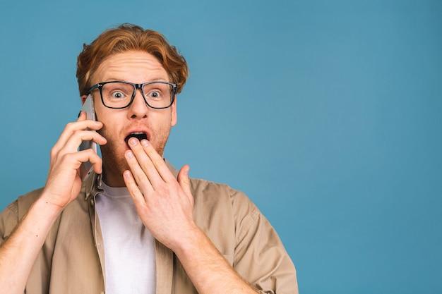 O, geweldig nieuws! glimlachend geschokt verbaasd jonge casual man praten op de mobiele telefoon