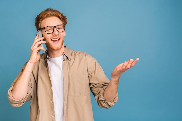O, geweldig nieuws! lachende casual jongeman praten op de mobiele telefoon