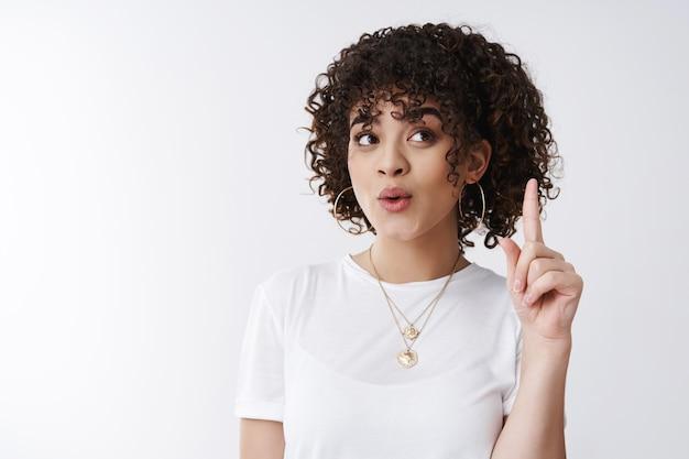 O heb een idee. meisje eindelijk oplossing gevonden uitstekend plan wijsvinger opsteken eureka gebaar lippen vouwen opzoeken wenkbrauwen optillen hebben perfecte suggestie creatieve vrouwelijke collega gedachten delen