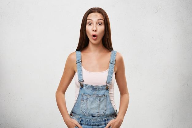 O mijn god. portret van grappige geschokte jonge europese vrouw met donker steil haar dat wenkbrauwen opheft en mond vol ongeloof opent