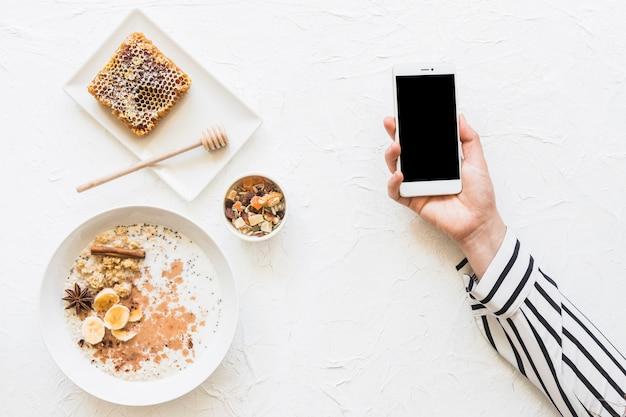 Oatmeals; dryfruits en honingraat op tafel met mobiele telefoon in handen