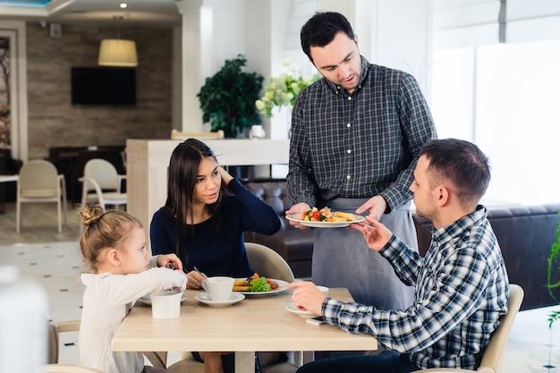 Ober bedient een gezin in een restaurant en brengt een vol bord
