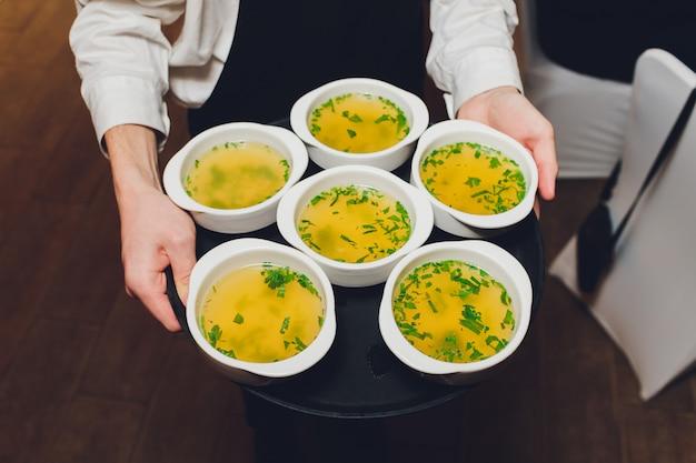 Ober bedrijf dienblad met platen soep in het restaurant.