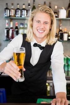 Ober bedrijf glas bier bij toog