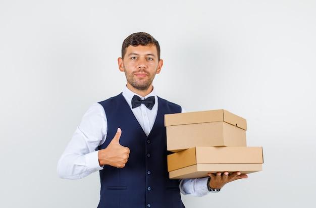 Ober bedrijf kartonnen dozen met duim omhoog in shirt, vest en op zoek tevreden. vooraanzicht.
