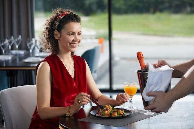 Ober brengt champagne in emmer met ijs naar een jonge vrouw in restaurant