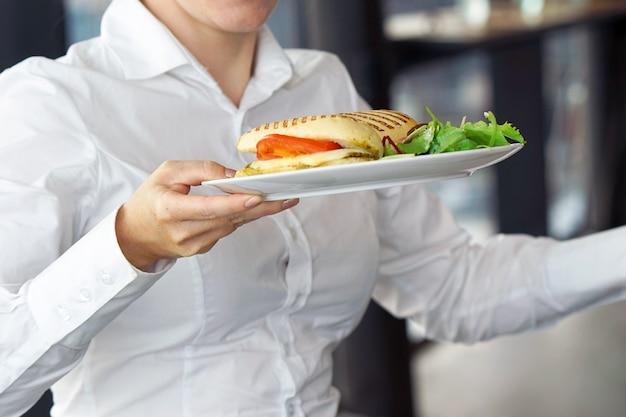 Ober die een bord met een bestelling op een feestelijk evenement, feest of bruiloft draagt.