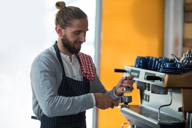 Ober gebruikt een stamper om gemalen koffie in een filterhouder te drukken
