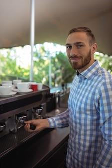 Ober gebruikt stamper om gemalen koffie in een filterhouder te persen