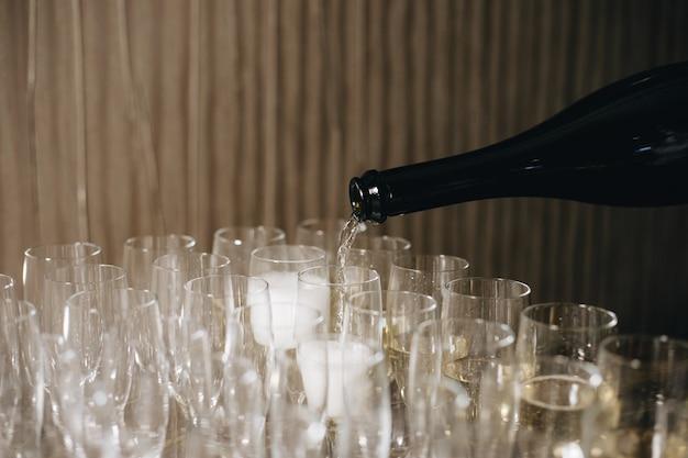 Ober giet champagne in glazen, champagne