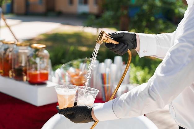 Ober giet cider in plastic bekers van de badkamerkraan