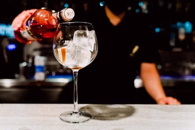 Ober giet een alcoholische drank in een leeg kristalglas