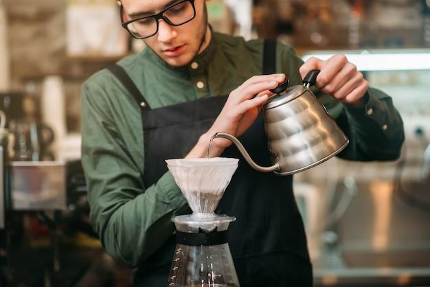 Ober giet heet gekookt water in een koffiepot