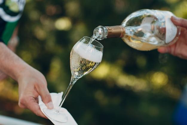 Ober gieten champagne in een glas