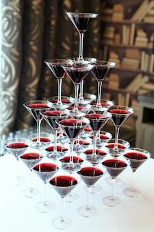 Ober gieten rode wijn of champagne in glazen voor feest.