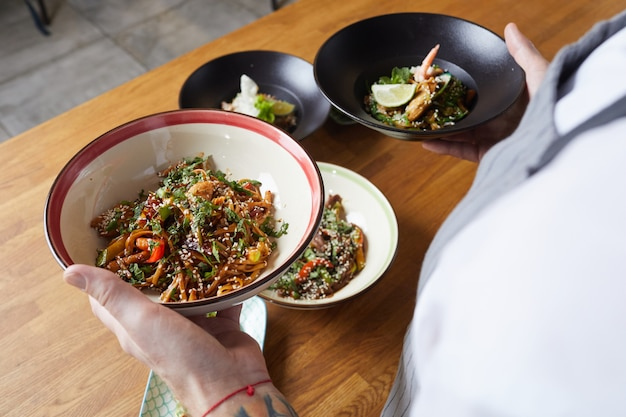Ober holding delicious oriental dishes