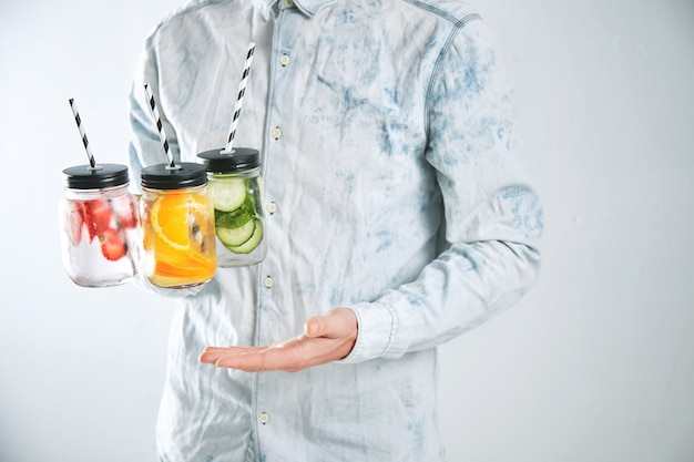 Ober houdt drie koude verfrissende drankjes van aardbei, sinaasappel, limoen, munt, komkommer, ijs en bruisend water in rustieke potten met rietjes erin