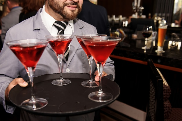 Ober in grijze jas draagt cocktailglazen met rode drankjes