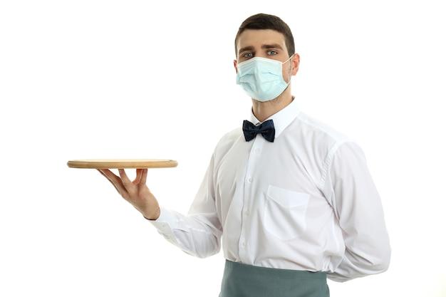 Ober in masker houdt dienblad, geïsoleerd op een witte achtergrond.