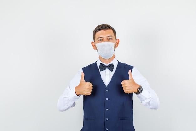 Ober in overhemd, vest, masker duimen opdagen en voorzichtig, vooraanzicht kijken.