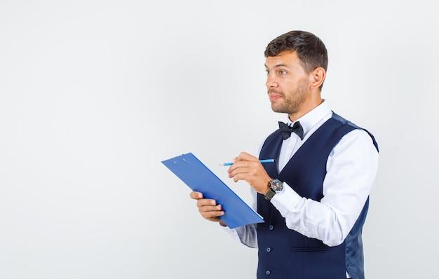Ober in shirt, vest notities maken op klembord en hoopvol, vooraanzicht kijken.