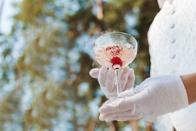 Ober in witte handschoenen geeft wijnglas met shampagne, rode kersen en witte rook van droogijs en geeft aan klant