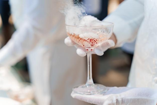 Ober in witte handschoenen houdt wijnglas met mousserende wijn, rode kersen en witte rook van droogijs en geeft aan de klant