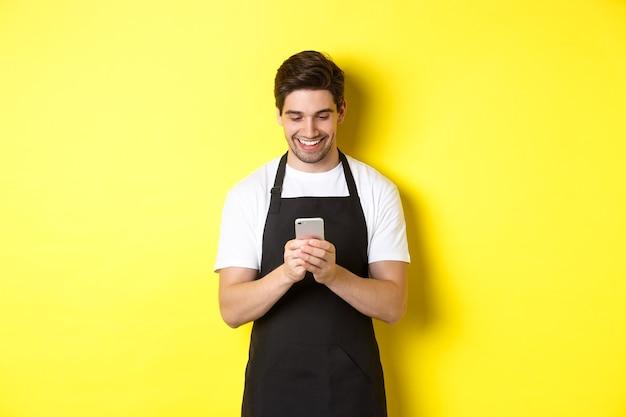 Ober in zwarte schort leest bericht op mobiele telefoon, glimlachend gelukkig, staande over gele achtergrond.