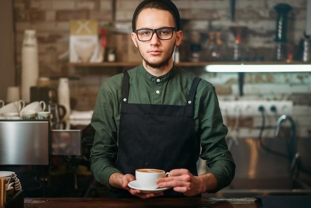 Ober in zwarte schort strekt zich uit een kopje koffie
