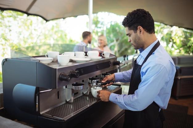 Ober maken kopje koffie uit espressomachine
