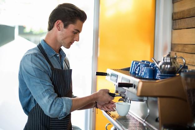 Ober maken van kopje koffie aan balie