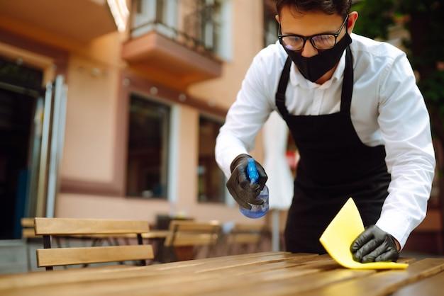 Ober met beschermend masker en handschoenen die de restauranttafel desinfecteren voor de volgende klant.