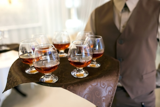 Ober met een dienblad verwelkomt bezoekers, gevulde glazen cognac