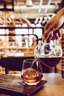 Ober met koude zwarte koffiepot met glas en ijs in coffeeshop