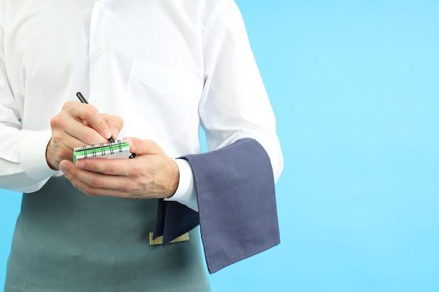 Ober met notitieboekje op blauwe achtergrond, ruimte voor tekst.