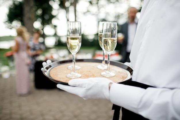 Ober met schotel van champagne en wijnglazen op een dienblad