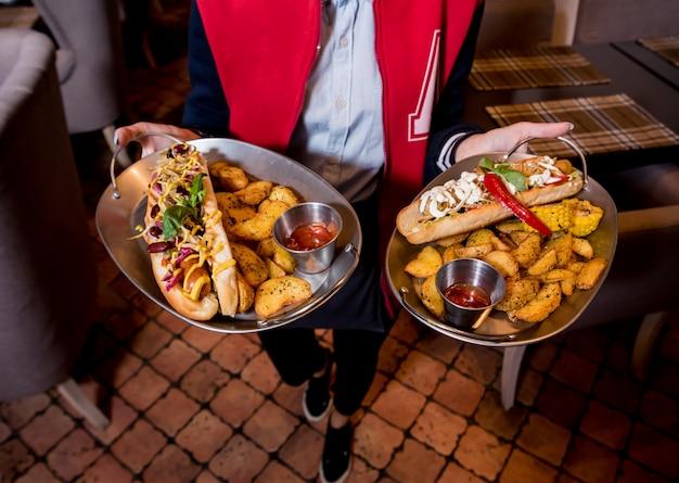 Ober, met twee borden met grote hotdogs en frietjes.