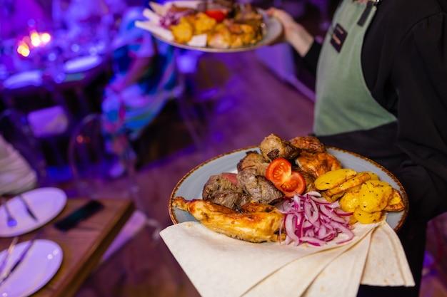Ober met twee borden met vleesgerecht op een feestelijk evenement, feest, huwelijksreceptie of verzorgd evenement.