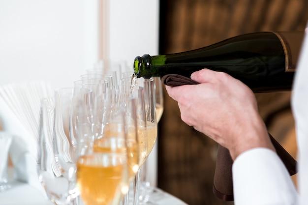 Ober schenkt champagne in. rij glazen bij de viering