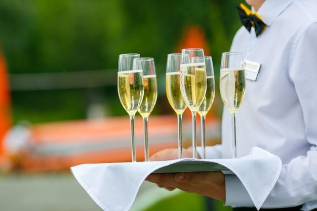 Ober schenkt een paar glazen champagne op dienblad