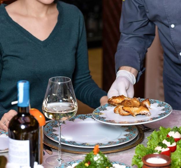 Ober serveert een kippenvlees aan de vrouw