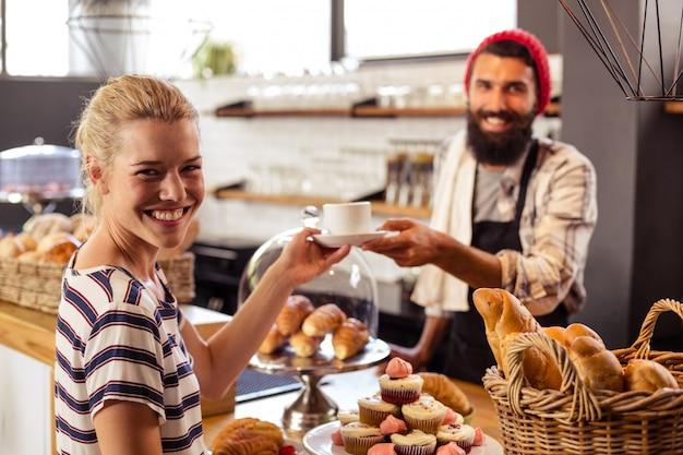 Ober serveert een koffie aan een klant