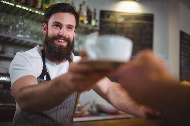 Ober serveert een kopje koffie aan de klant