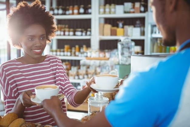 Ober serveren een kopje koffie aan een vrouw