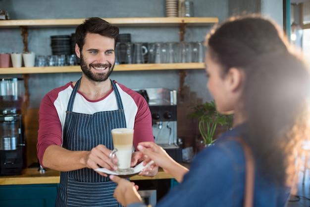 Ober serveren een kopje koude koffie aan de klant aan balie